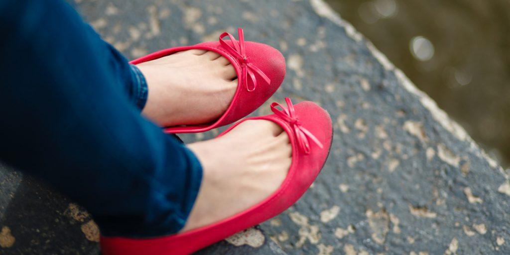 Naisen jalat punaisissa pikkukengissä.