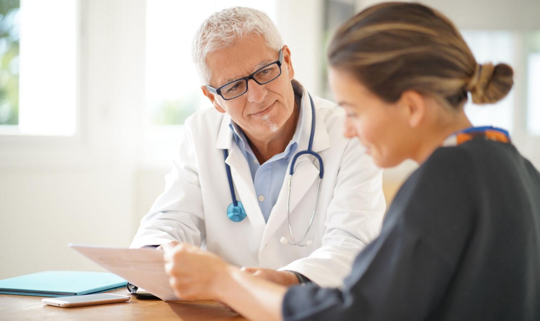 Lääkäri katsoo potilasta vastaanotolla ymmärtäväisesti