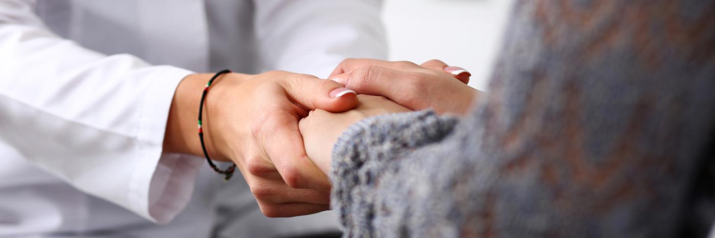lääkärin ja potilaan kädet yhdessä