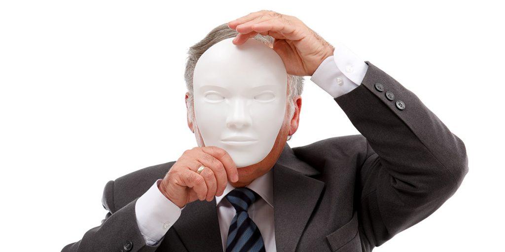 Mies pitää naamaria kasvojen edessä