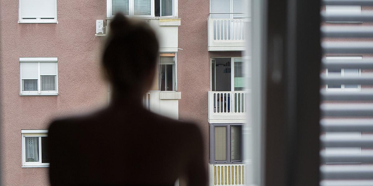 Naisen siluetti katsoo ikkunasta kerrostalon seinää, jossa ikkunoita ja parvekkeita.